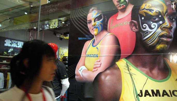Pictures with images of Peking Opera masks painted on the faces of Usain Bolt, Beijing Olympic gold medalist from Jamaica and other athletes appear on a Beijing street.